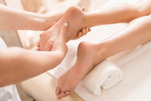 cropped view of woman relaxing and having feet massage in massage salon